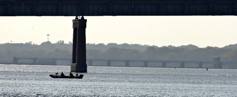 Photo of fishermen under a bridge